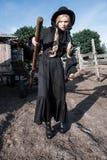 Forme a la mujer joven que lleva el vestido y el sombrero negros elegantes en el campo Estilo de la moda de Amish Imagenes de archivo
