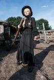 Forme a la mujer joven que lleva el vestido y el sombrero negros elegantes en el campo Estilo de la moda de Amish Fotos de archivo libres de regalías
