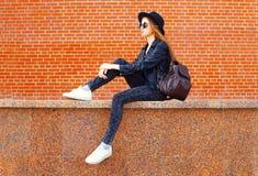 Forme a la mujer joven que lleva un estilo negro de la roca que se sienta sobre fondo de los ladrillos en perfil Imagen de archivo libre de regalías