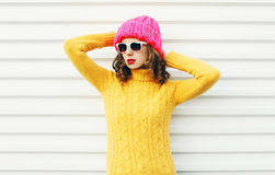 Forme a la mujer joven que lleva un sombrero rosado hecho punto, suéter colorido amarillo sobre blanco Imágenes de archivo libres de regalías