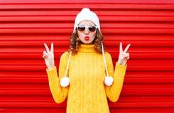 Forme a la mujer joven que sopla los labios rojos que llevan un sombrero amarillo hecho punto colorido del suéter sobre rojo Fotos de archivo