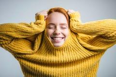 Forme a la mujer joven que tira del suéter amarillo y que se divierte sobre el fondo blanco Imagen de archivo