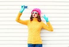 Forme a la mujer joven que toma el autorretrato de la imagen en smartphone sobre blanco Fotografía de archivo