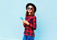 Forme a la mujer joven que usa la ciudad del smartphone n, el sombrero negro que lleva y la camisa a cuadros roja Fotos de archivo libres de regalías