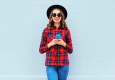 Forme a la mujer joven que usa smartphone al aire libre en la ciudad, llevando la camisa a cuadros roja del sombrero negro Foto de archivo