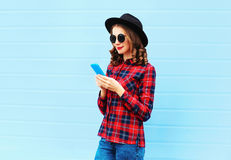 Forme a la mujer joven que usa smartphone en la ciudad, llevando la camisa a cuadros roja del sombrero negro sobre fondo azul Fotos de archivo