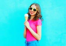 Forme a la mujer joven sonriente con helado sobre azul colorido Fotos de archivo