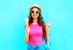 Forme a la mujer joven sonriente con helado sobre azul colorido del sombrero de paja que lleva Foto de archivo