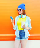 Forme a la mujer joven sonriente con una taza de café usando smartphone sobre naranja colorida Imágenes de archivo libres de regalías
