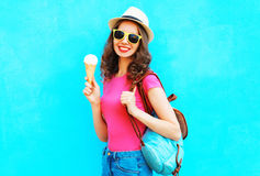 Forme a la mujer joven sonriente del retrato con helado sobre azul colorido Imagenes de archivo