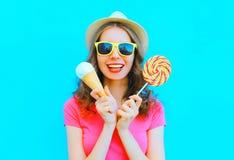 Forme a la mujer joven sonriente feliz con helado y la piruleta sobre azul colorido Imagen de archivo