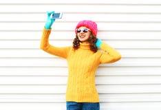 Forme a la mujer joven sonriente feliz que toma el autorretrato de la imagen en smartphone sobre blanco Fotografía de archivo