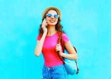 Forme a la mujer joven sonriente que habla en un smartphone sobre un fondo azul colorido Foto de archivo libre de regalías
