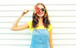 Forme a la mujer joven sonriente que lleva a cabo una rebanada de sandía bajo la forma de helado Foto de archivo