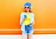 Forme a la mujer joven sonriente que usa smartphone con una taza de café sobre colorido Imagen de archivo libre de regalías