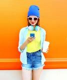 Forme a la mujer joven sonriente que usa smartphone con una taza de café sobre naranja colorida Fotografía de archivo
