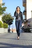 Forme a la mujer que camina en la calle que habla en el teléfono móvil Imagen de archivo