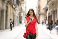 Forme a la mujer que camina y que usa un teléfono elegante Foto de archivo libre de regalías