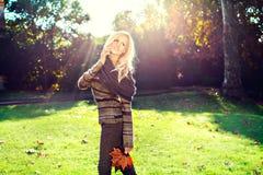 Forme a la mujer que habla y que camina en un parque Foto de archivo libre de regalías