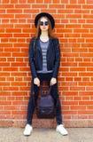 Forme a la mujer que lleva un estilo negro de la roca que presenta en ciudad sobre fondo de los ladrillos Fotos de archivo libres de regalías