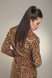 Forme a la mujer que lleva una capa del estampado de animales que mira abajo Imagenes de archivo