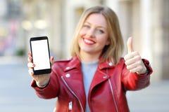 Forme a la mujer que muestra una pantalla del smartphone en la calle Fotografía de archivo libre de regalías