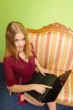 Forme a la mujer que se sienta en el sofá usando el ordenador portátil de la PC Fotos de archivo