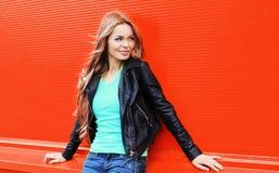 Forme a la mujer rubia bastante joven que lleva un estilo negro de la roca que mira en perfil sobre rojo colorido Foto de archivo