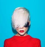 Forme la mujer rubia con el peinado de moda y las gafas de sol en un bl Foto de archivo libre de regalías