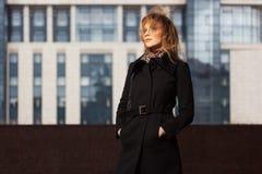 Forme a la mujer rubia en capa negra en la calle de la ciudad Foto de archivo libre de regalías