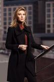 Forme a la mujer rubia en capa negra que camina en la calle de la ciudad Foto de archivo libre de regalías
