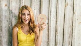 Forme a la mujer rubia joven en camiseta amarilla sobre fondo de madera pálido Fotografía de archivo