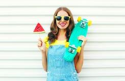 Forme a la mujer sonriente alegre con una rebanada de monopatín del helado de la sandía Fotografía de archivo