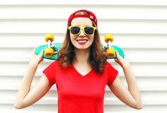 Forme a la mujer sonriente bastante fresca con el monopatín sobre blanco Fotografía de archivo libre de regalías
