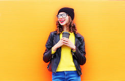 Forme a la mujer sonriente bastante joven con la taza de café que lleva un sombrero negro, chaqueta de la roca sobre naranja colo Fotografía de archivo libre de regalías