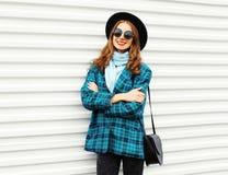 Forme a la mujer sonriente bastante joven que lleva la chaqueta de la capa del sombrero negro con el bolso sobre blanco Imagen de archivo