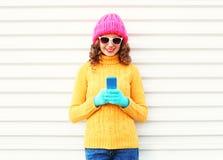 Forme a la mujer sonriente bastante joven que usa el smartphone que lleva la ropa hecha punto colorida sobre blanco Imágenes de archivo libres de regalías