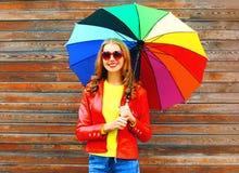 Forme a la mujer sonriente con el paraguas colorido en día del otoño Fotografía de archivo