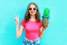 Forme a la mujer sonriente con las gafas de sol de la piña que se divierten sobre azul colorido Fotos de archivo libres de regalías