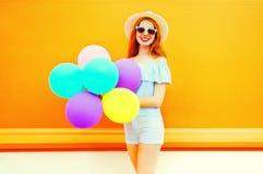 Forme a la mujer sonriente con los globos coloridos de un aire en una naranja Imagen de archivo libre de regalías