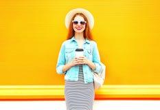 Forme a la mujer sonriente con la taza de café en fondo anaranjado Foto de archivo libre de regalías