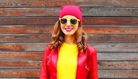 Forme a la mujer sonriente del otoño que lleva un sombrero rojo de la chaqueta de cuero Foto de archivo libre de regalías