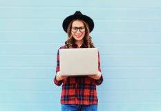 Forme a la mujer sonriente joven que sostiene el ordenador portátil en la ciudad, llevando un sombrero negro, camisa a cuadros ro Fotos de archivo
