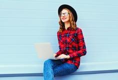 Forme a la mujer sonriente joven que trabaja usando el ordenador portátil al aire libre Imágenes de archivo libres de regalías