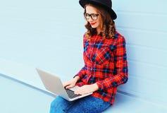 Forme a la mujer sonriente joven que trabaja usando el ordenador portátil en ciudad Imagen de archivo libre de regalías
