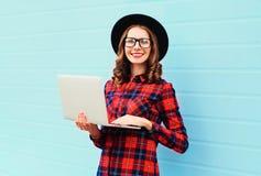 Forme a la mujer sonriente joven que usa el ordenador portátil en la ciudad, llevando un sombrero negro, camisa a cuadros roja Fotos de archivo