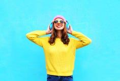 Forme a la mujer sonriente que escucha la música en auriculares Fotografía de archivo libre de regalías