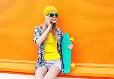 Forme a la mujer sonriente que habla en smartphone con el monopatín sobre naranja colorida Imagen de archivo