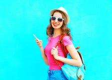 Forme a la mujer sonriente que usa smartphone en sombrero de paja de la ciudad y mochila que llevan sobre azul colorido Foto de archivo libre de regalías