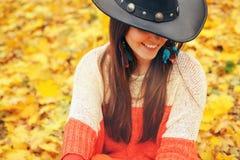 Forme a la mujer sonriente vestida en sombrero elegante del estilo del boho, tome un resto en parque del otoño Imágenes de archivo libres de regalías